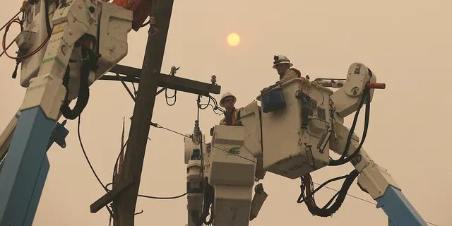Pacific Gas & Electric crews work to restore power lines Friday, Nov. 9, 2018, in Paradise, Calif. (AP Photo/Rich Pedroncelli)