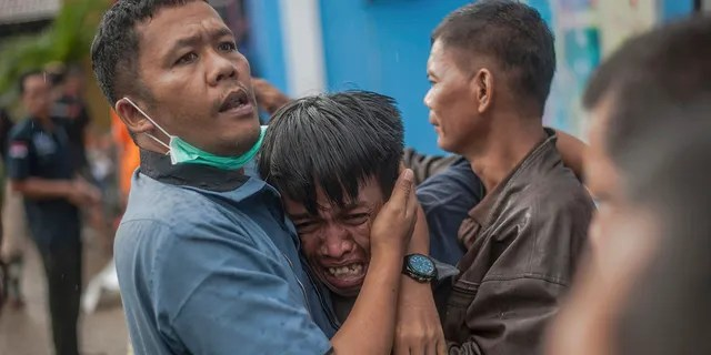 A man reacts after identifying his relative among the bodies of tsunami victims in Carita, Indonesia, Sunday. (AP Photo/Fauzy Chaniago)