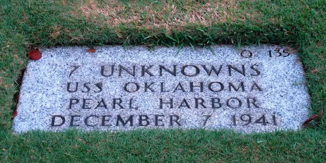 The National Memorial Cemetery of the Pacific in Honolulu displays a gravestone identifying it as the resting place of seven unknown people from the USS Oklahoma who died in Japanese bombing of Pearl Harbor.
