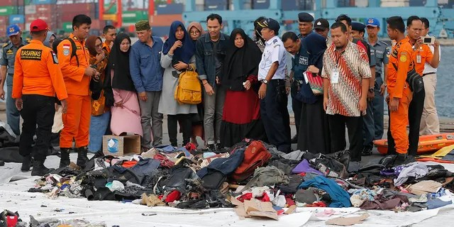 Relatives of passengers of a crashed Lion Air jet check personal belongings retrieved from the waters where the airplane is believed to have crashed, at Tanjung Priok Port in Jakarta, Indonesia. (AP Photo/Tatan Syuflana, File)