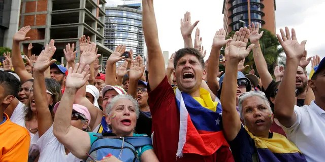 Anti-government protesters cheer after Juan Guaido, head of Venezuela's opposition-run congress, declares himself interim president of the South American country.