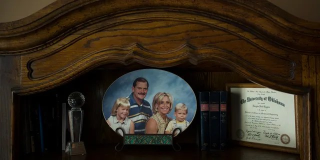 Landon Biggers sits on his mother's lap in an old family photo in his father's home office in La Quinta, Calif.