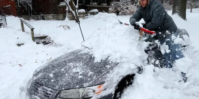 Jeff Clifford digs out his girlfriend's car from a pile of snow on Saturday, Jan. 12, 2019, in St. Louis.
