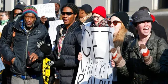 Demonstrators hold signs and chant outside the Governors office at the Capitol in Richmond, Va., Saturday, Feb. 2, 2019. The demonstrators are calling for the resignation of Virginia Governor Ralph Northam after a 30 year old photo of him on his medical school yearbook photo was widely distributed Friday.