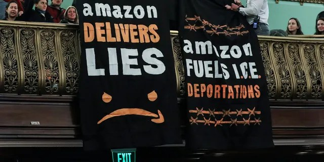 Protesters unfurl anti-Amazon banners from the balcony of a hearing room during a New York City Council Finance Committee hearing titled 'Amazon HQ2 Stage 2: Does the Amazon Deal Deliver for New York City Residents?' at New York City Hall, Jan. 30, 2019. (Photo by Drew Angerer/Getty Images)