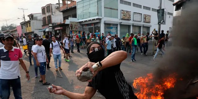 A demonstrator throws rocks during clashes with the Bolivarian National Guard in Urena, Venezuela, near the border with Colombia, Saturday, Feb. 23, 2019