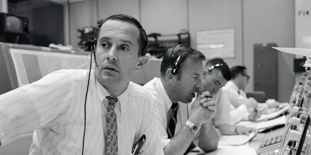 Spacecraft communicators are pictured as they keep in contact with the Apollo 11 astronauts during their lunar landing mission on July 20, 1969. From left to right are astronauts Charles M. Duke Jr., James A. Lovell Jr. and Fred W. Haise Jr. (NASA)