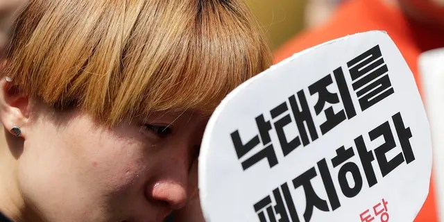 A woman wipes tears during a rally demanding the abolition of abortion law outside of the Constitutional Court in Seoul, South Korea on Thursday. (AP Photo/Lee Jin-man)