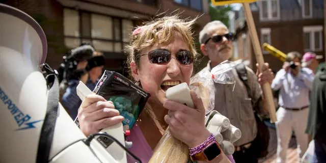 A member of the anti-war group Code Pink, and others attempt to bring food and supplies into the Venezuelan Embassy in Washington on Thursday. (AP Photo/Andrew Harnik)