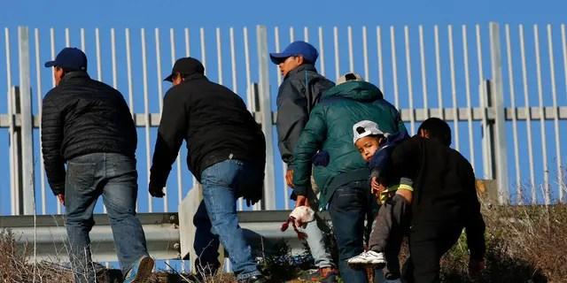 ARCHIVO: migrantes hondureños, uno de ellos con un niño, que planean entregarse a los agentes de la patrulla fronteriza de los Estados Unidos, caminan por el terraplén después de escalar el muro fronterizo de los Estados Unidos desde Tijuana, México.