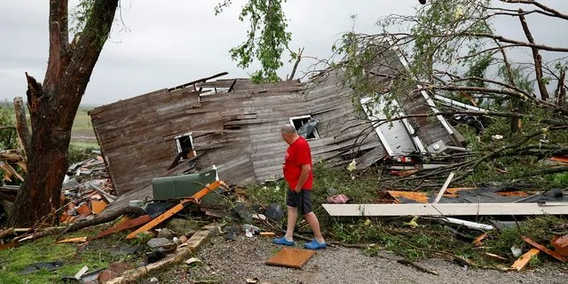 Joe Armison looking over his destroyed barn after a tornado struck the outskirts of Eudora, Kan., on Tuesday. (AP Photo/Colin E. Braley)