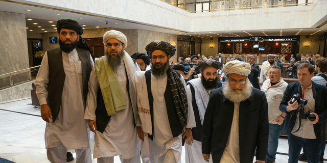 Mullah Abdul Ghani Baradar, the Taliban group's top political leader, third from left, arrives with other members of the Taliban delegation for talks in Moscow, Russia, Tuesday, May 28, 2019. Baradar and a team of 14 Taliban are in Moscow where they are scheduled to meet other Afghans including former President Hamid Karzai and some of the candidates in the presidential elections.