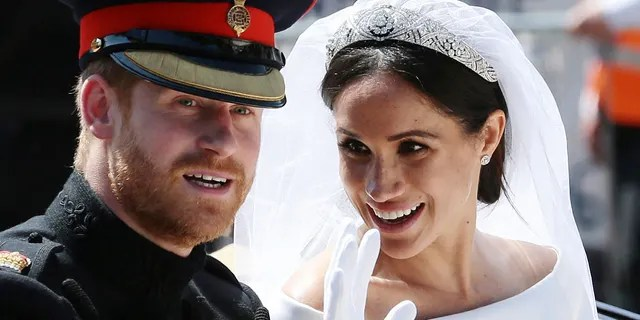In this Saturday, May 19, 2018 file photo Britain's Prince Harry and Meghan Markle ride in an open-topped carriage after their wedding ceremony at St. George's Chapel in Windsor Castle in Windsor, near London, England.