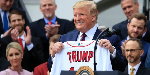 President Donald Trump shows off a Red Sox jersey presented to him during a ceremony welcoming the Boston Red Sox the 2018 World Series baseball champions to the White House, Thursday, May 9, 2019, in Washington. (Associated Press)