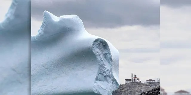 A huge iceberg passes by Cape Bonavista Lighthouse.