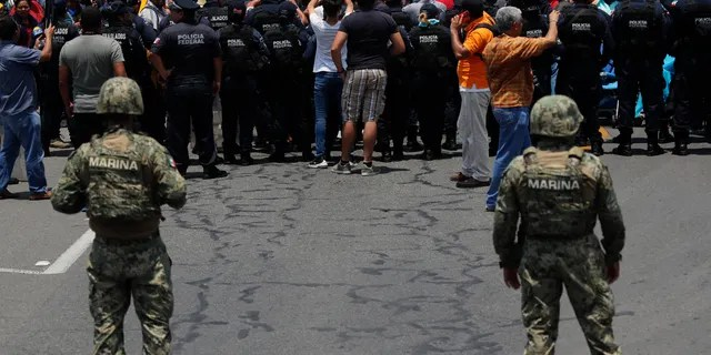 Mexican law enforcement stopping a migrant caravan that had crossed the Mexico-Guatemala border, near Metapa, Mexico, earlier this month. (AP Photo/Marco Ugarte, File)