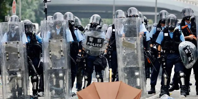 Police in riot gear block a street near the Legislative Council in Hong Kong, Wednesday.