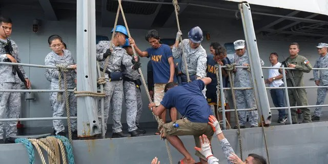 Rescued Filipino fishermen transfer to another ship as they head back to shore in Occidental Mindoro province, Philippines on Friday June 14, 2019.