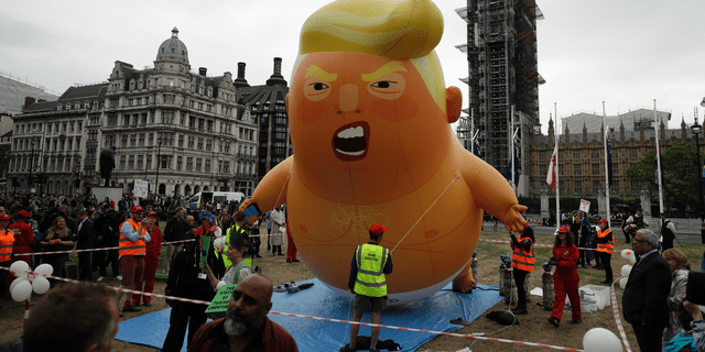 The 'Trump Baby' blimp was inflated in Parliament Square in central London as people gathered to demonstrate against the state visit of President Donald Trump, Tuesday, June 4, 2019. Trump joined British Prime Minister Theresa May for a day of talks on Tuesday. (AP Photo/Matt Dunham)