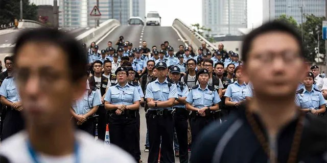 Police arriving to negotiate with protesters to clear a road in Hong Kong.