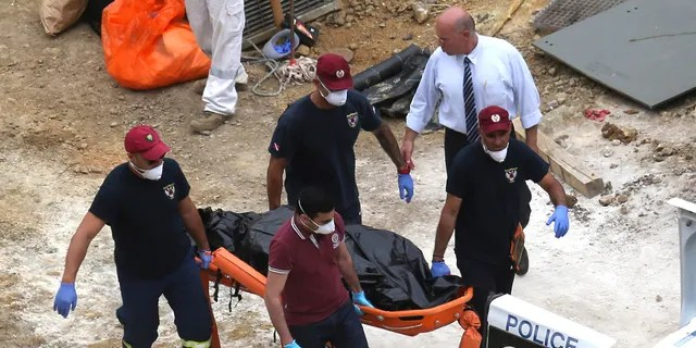 Cyprus Special Disaster Response Unit investigators carry a covered suitcase on a stretcher after it was retrieved from a man-made lake near the village of Mitsero, outside of the capital Nicosia, Cyprus, on June 4. Inside the suitcase is believed to be one of the victims of a 35-year-old Cypriot military officer. (AP Photo/Petros Karadjias)