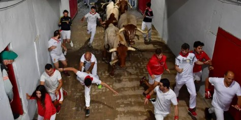 Revellers run next to fighting bulls during the running of the bulls at the San Fermin Festival, in Pamplona, northern Spain, Sunday, July 14, 2019.