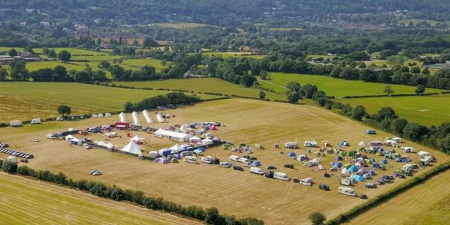 Drone pictures of the field near the Three Counties Showground show a red double-decker party bus and gazebo covering several double-beds.