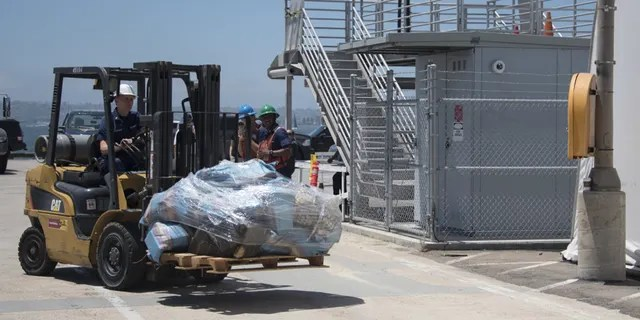 A crewmember of Coast Guard Cutter Steadfast uses a forklift to move a pallet of cocaine in San Diego, July 26, 2019.