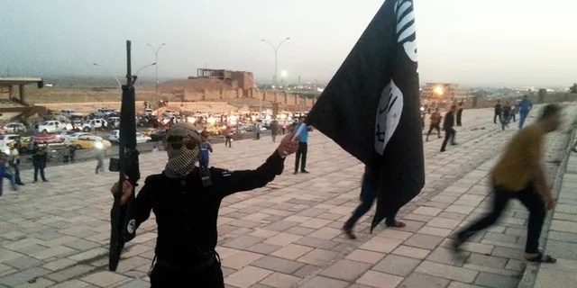 A fighter of the Islamic State of Iraq and the Levant (ISIL) holds an ISIL flag and a weapon on a street in the city of Mosul, June 23, 2014. U.S. Secretary of State John Kerry held crisis talks with leaders of Iraq's autonomous Kurdish region on Tuesday urging them to stand with Baghdad in the face of a Sunni insurgent onslaught that threatens to dismember the country.