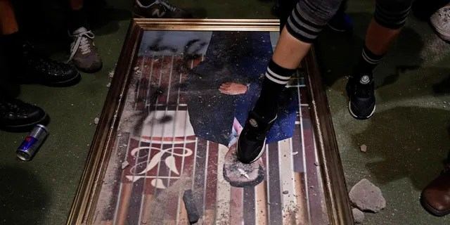 A protester steps on a damaged portrait of former legislative leader lie on the ground after protesters broke into the Legislative Council building in Hong Kong, Monday, July 1, 2019.