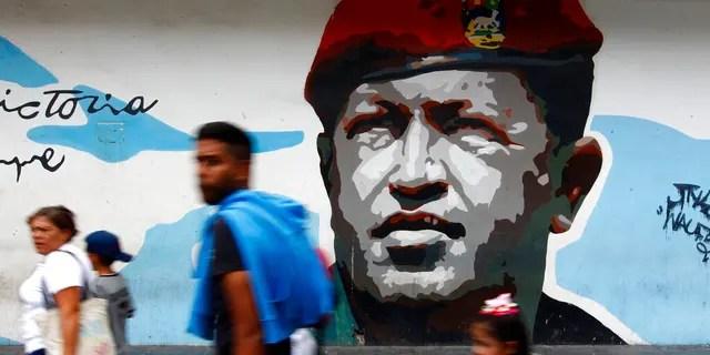 Pedestrians walk past a mural depicting the late President Hugo Chavez, in Caracas, Venezuela, Tuesday, Aug. 6, 2019.