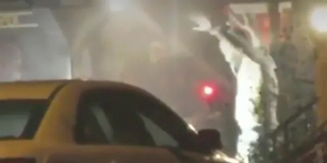 In this image from video taken by Bill Trenwith on Wednesday, Aug. 14, 2019, a Maurice Hill exits a building with hands up in Philadelphia, Pennsylvania.