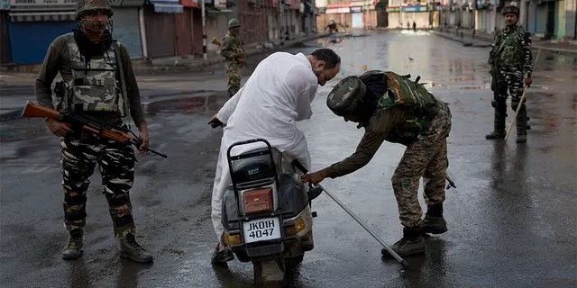 Indian Paramilitary soldiers check the bag of a man riding a scooter during curfew in Indian controlled Kashmir, Thursday, Aug. 8, 2019. (AP Photo/Dar Yasin)