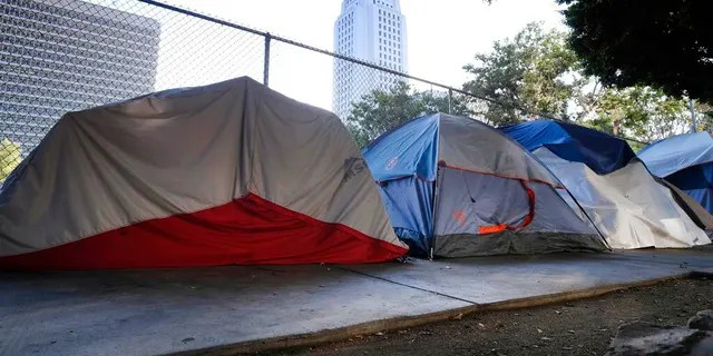 Los Angeles City Hall behind a homeless tent encampment along a street in downtown Los Angeles this past July. (AP Photo/Richard Vogel, File)