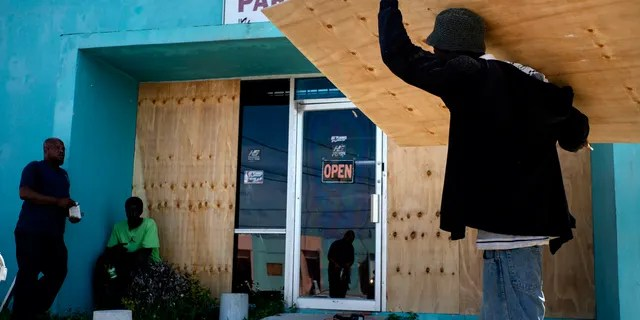 Workers board up a shop's window front as they make preparations for the arrival of Hurricane Dorian, in Freeport, Bahamas.