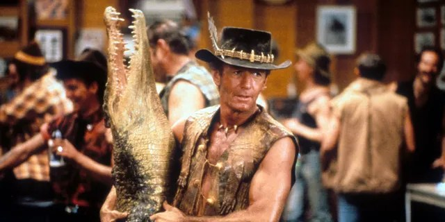 Paul Hogan carrying dead crocodile in bar in a scene from the film 'Crocodile Dundee', 1986.
