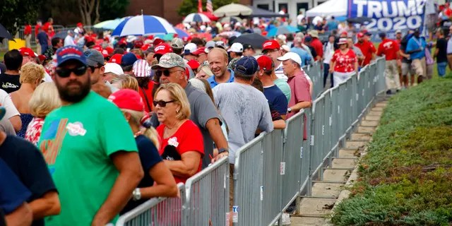 Attendees line up outside hours before President Donald Trump speaks at a campaign rally in Fayetteville, N.C., Monday Sept. 9, 2019 (AP Photo/Chris Seward)