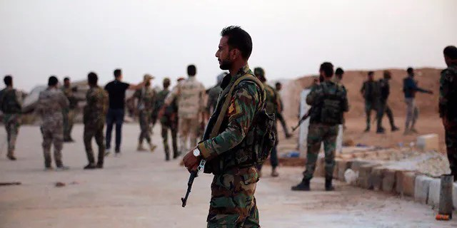 In this Monday, Oct. 14, 2019, photo, released by the Syrian official news agency SANA, Syrian troops deploy in the Tabqa airbase in Raqqa, Syria. SANA said Monday that in addition to Tabqa and its airbase that carries the same name, Syrian troops entered several other villages on the southern parts of Raqqa province. (SANA via AP)