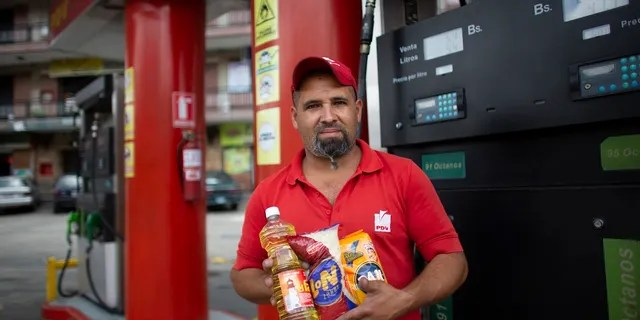 In this Oct. 8, 2019 photo, gas station attendant Leowaldo Sanchez poses with food items he was paid with by motorists: a bottle of cooking oil, a kilogram of rice and a package of corn flour, as he works at the pump in San Antonio de los Altos on the outskirts of Caracas, Venezuela. Bartering at the pump has taken off as hyperinflation makes Venezuela's paper currency, the bolivar, hard to find and renders some denominations all but worthless, so that nobody will accept them. (AP Photo/Ariana Cubillos)