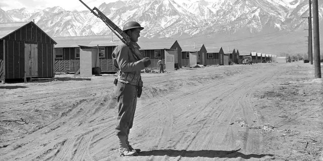 In this May 23, 1943, file photo, an American soldier guards a Japanese internment camp at Manzanar, Calif.