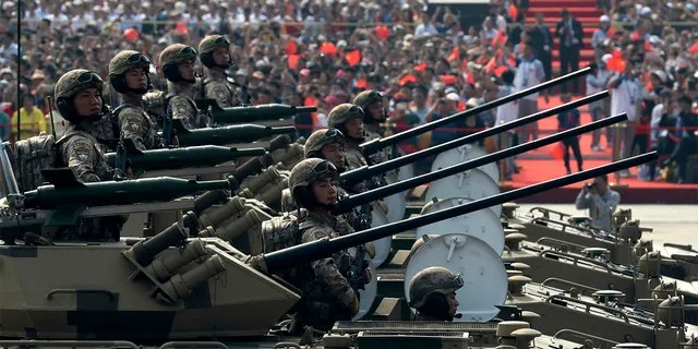 Military vehicles roll down during a parade to commemorate the 70th anniversary of the founding of Communist China in Beijing, Tuesday, Oct. 1, 2019. (AP Photo/Ng Han Guan)
