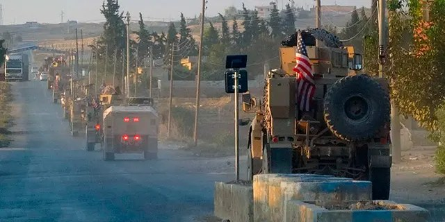 In this image provided by Hawar News Agency, ANHA, U.S. military vehicles travel down a main road in northeast Syria on Oct. 7. U.S.-backed Kurdish-led forces in Syria said American troops began withdrawing Monday from their positions along Turkey's border in northeastern Syria, ahead of an anticipated Turkish invasion that the Kurds say will overturn five years of achievements in the battle against the Islamic State group. (ANHA via AP)