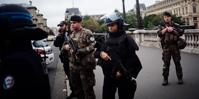 Armed police officers and soldiers patrol after a knife attack at the police headquarters in Paris. (AP Photo/Kamil Zihnioglu)