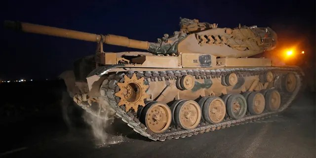 A Turkish army tank is driven to its new position, after was uploaded from a truck, on the Turkish side of the border between Turkey and Syria, in Sanliurfa province, on Tuesday.
