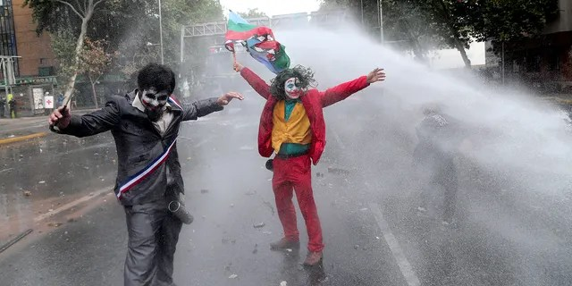 "Men dressed as clowns, one dressed as the the movie character ""The Joker"" flying a Mapuche indigenous flag, are sprayed by a police water cannon during an anti-government protest in Santiago, Chile, Monday, Nov. 4, 2019."