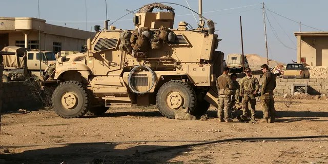 In this Feb. 23, 2017, photo, U.S. Army soldiers stand outside their armored vehicle on a joint base with the Iraqi Army south of Mosul, Iraq. (AP Photo/ Khalid Mohammed, File)