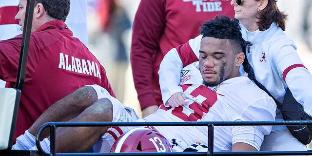 Tua Tagovailoa #13 of the Alabama Crimson Tide is helped off the field after being injured on a play in the first half of a game against the Mississippi State Bulldogs at Davis Wade Stadium on November 16, 2019 in Starkville, Mississippi.