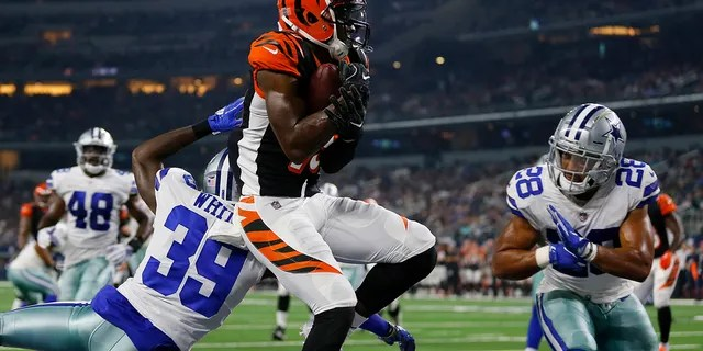 File-This Aug. 18, 2018 file photo shows Cincinnati Bengals wide receiver John Ross, center, making a catch to complete a two point conversion between Dallas Cowboys cornerback Marquez White (39) and safety Jameill Showers (28) during a preseason NFL Football game in Arlington, Texas. (AP Photo/Roger Steinman, File)