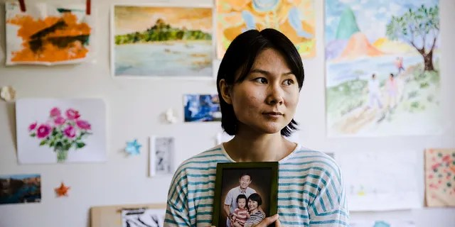 In this Wednesday, May 9, 2018 file photo, Hua Qu, the wife of detained Chinese-American Xiyue Wang, poses for a photograph with a portrait of her family in Princeton, N.J. Iran's foreign minister says a detained Princeton graduate student will be exchanged for an Iranian scientist held by the U.S. Mohammed Javad Zarif made the announcement on Twitter on Saturday, Dec. 7, 2019.