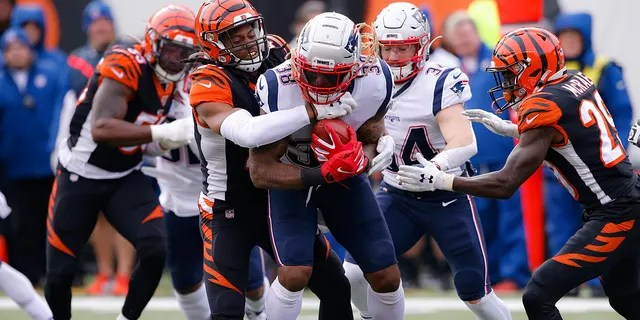 New England Patriots running back Brandon Bolden (38) is tackled by Cincinnati Bengals cornerback Darius Phillips, center left, in the first half of an NFL football game, Sunday, Dec. 15, 2019, in Cincinnati.